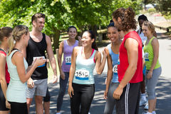 Runners chatting after race in park Stock Image