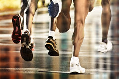 Runners city reflections. Runners on wet ground with city reflection Royalty Free Stock Photography