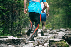 Runners climb uphill along the muddy Stock Photos
