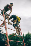 Runners climbing structure in a test of extreme obstacle race Royalty Free Stock Images