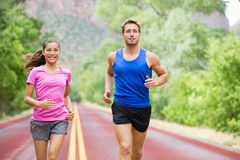 Runners couple in jogging exercise outside. On road in beautiful nature training for marathon run. Multiracial sports couple, Asian women sport model and men stock photography