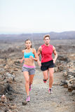 Runners couple running on trail in cross country. Run outdoors training for marathon or triathlon. Fit young fitness model men and asian women training together royalty free stock photo