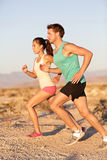 Runners couple running in trail run outside. Runners couple running in trail run. Runner men and sport women training and jogging outside in cross country run Stock Image