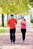 Runners couple sport. Runners couple running on trail in cross country run outdoors training on jogging track, Fit young fitness model men and asian women royalty free stock photos