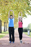 Runners couple sport. Runners couple running on trail in cross country run outdoors training on jogging track, Fit young fitness model men and asian women Stock Images