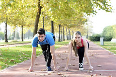Runners couple sport. Runners couple running on trail in cross country run outdoors training on jogging track, Fit young fitness model men and asian women Stock Photos