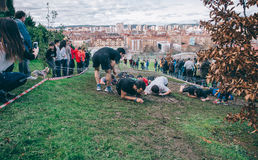 Runners crawling under barbed wire in a test of extreme obstacle race Royalty Free Stock Photography