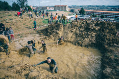 Runners crossing mud pit in a test of extreme obstacle race Stock Images