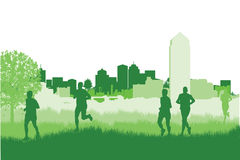 Runners in a field. On a cityscape background Royalty Free Stock Photography