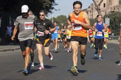Runners foreground and several runners in background Stock Photos
