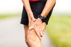 Runners leg knee pain injury. Runner holding sore leg, knee pain from running or exercising, jogging injury or cramp, cross country in summer nature Royalty Free Stock Images