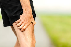 Runners leg pain injury. Runner holding sore leg, pain from running or exercising, jogging injury or cramp, cross country in summer nature Royalty Free Stock Image