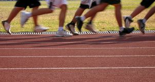 Runners in Motion. Exercising on an outdoor athletic running track Stock Photos