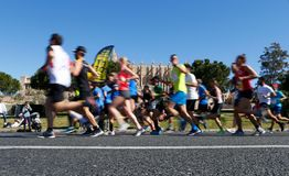 Runners during palma half marathon passing next to palma cathedral low speed. Runners pass next to Palma de Mallorca cathedral during the half Marathon race in royalty free stock image