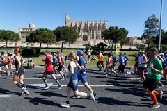 Runners during palma half marathon passing next to palma cathedral. Runners pass next to Palma de Mallorca cathedral during the half Marathon race in the Spanish royalty free stock photo