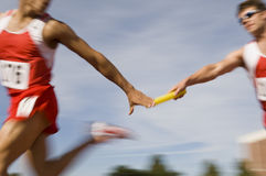 Runners Passing Baton In Relay Race. Blurred motion male runners passing baton in relay race stock image