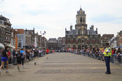 Runners passing city hall in historic Delft Royalty Free Stock Images