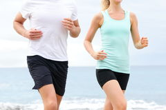 Runners - people running on beach midsection. Runners - people running on beach. Midsection close up of unrecognizable young couple jogging training at boardwalk stock photos