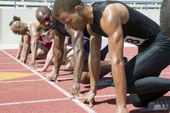 Runners Preparing For Race. Multiethnic runners preparing for race at starting blocks Royalty Free Stock Images