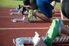 Runners preparing for race at starting blocks Royalty Free Stock Image