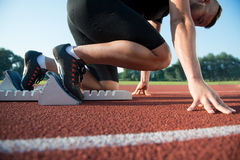 Runners preparing for race at starting blocks Stock Photos