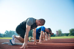 Runners preparing for race at starting blocks Royalty Free Stock Images
