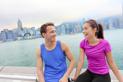 Runners relaxing after workout in Hong Kong city. Running caucasian and asian men and women post run taking a break talking together on the Avenue of the Stars Stock Image