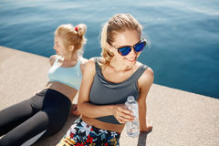 Runners resting taking a break drinking water after running Royalty Free Stock Photography