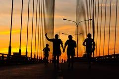 Runners run on bridge in the morning Stock Photo