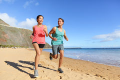 Runners running on beach - jogging couple Stock Image