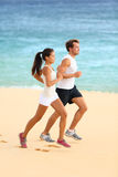 Runners running on beach - jogging couple. Runners running on beach. Jogging couple training on beach in full body length living healthy active lifestyle. Asian Stock Photos