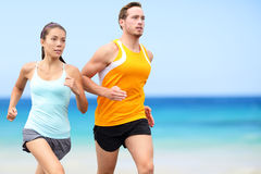 Runners running on beach - jogging couple. Runners running on beach. Jogging couple training on beach in full body length living healthy active lifestyle. Asian royalty free stock images