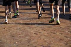 Runners running on paved street Stock Photos