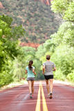 Runners running on road in nature away from camera. Couple, women and men jogging for a run outside in amazing mountain landscape. Full body length rear view Royalty Free Stock Photography