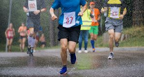 Runners running under rain drops city marathon royalty free stock image
