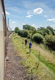 Pair of maie, adult runners running alongside a famous steam locomotive. The runners are seen on a path which runs adjacent to the railway track in which royalty free stock photography
