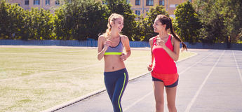Runners on the stadium track. Women summer fitness workout Royalty Free Stock Photos