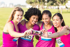 Runners supporting breast cancer marathon and taking selfies Stock Photos