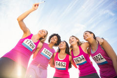 Runners supporting breast cancer marathon and taking selfies. In parkland stock photography