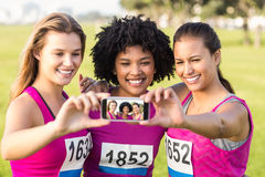 Runners supporting breast cancer marathon and taking selfies Royalty Free Stock Photography