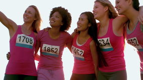 runners supporting breast cancer marathon and taking selfies in parkland stock video footage