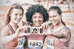Runners supporting breast cancer marathon and taking selfies. In parkland Royalty Free Stock Photography