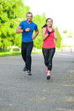 Runners training outdoors working out. City. Running couple jogging outside. City sport training in green park Royalty Free Stock Photo