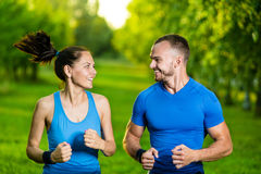 Runners training outdoors working out. City. Running couple jogging outside. City sport training in green park Stock Photo