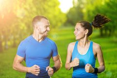Runners training outdoors working out. City. Running couple jogging outside. City sport training in green park Royalty Free Stock Photography