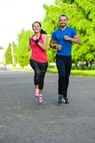 Runners training outdoors working out. City. Running couple jogging outside. City sport training in green park Royalty Free Stock Images