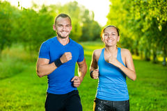 Runners training outdoors working out. City. Running couple jogging outside. City sport training in green park Stock Image