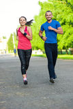 Runners training outdoors working out. City. Running couple jogging outside. City sport training in green park Stock Images