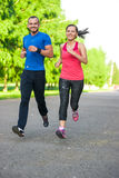 Runners training outdoors working out. City. Running couple jogging outside. City sport training in green park Royalty Free Stock Image