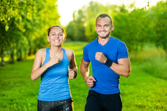 Runners training outdoors working out. City. Running couple jogging outside. City sport training in green park Royalty Free Stock Photos